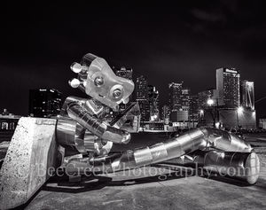 Dallas, traveling man, sitting sculpture, banjo, robo, skyline, skylines, cityscape, cityscapes, downtown,  modern, urban, night, robot, deep ellum, mass trasit, train, nuts, bolts,