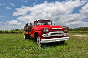 Hill country winery, bright red truck, wine, barrels, grapes, grape vines, clouds, blue sky, texas hill country, truck,