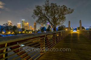 Houston cityscape, Police Memorial, pedestrian bridge, dark, city, Buffalo Bayou, moon lights, faint blue glow, trees, path, houston stock,