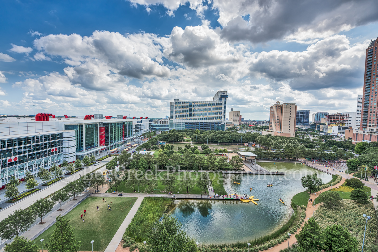 Houston, Discovery Green Park, George Brown Convention Center, water fountain, spray fountain, Kinder lake, Avenida Plaza, high rise condos, hotels, downtown, city, cityscape, people,, photo