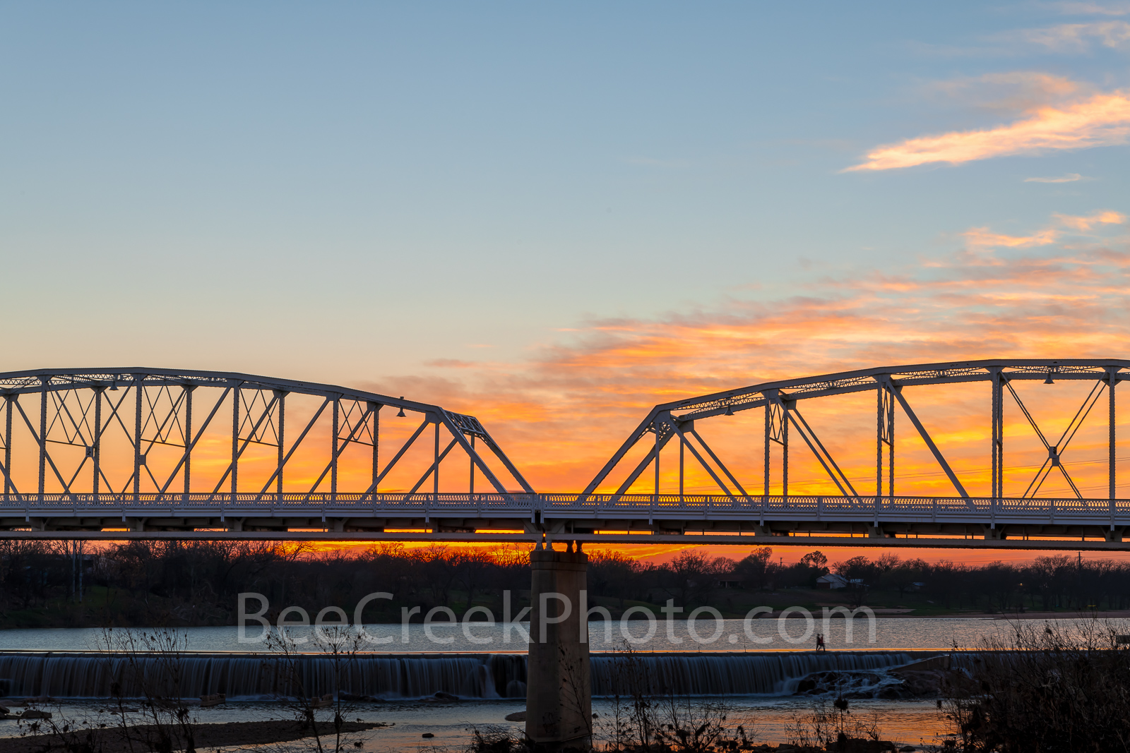 Llano Bridge at Sunset - The Llano bridge in the Texas Hill Country as the sunset in the west. The Llano river runs through this...