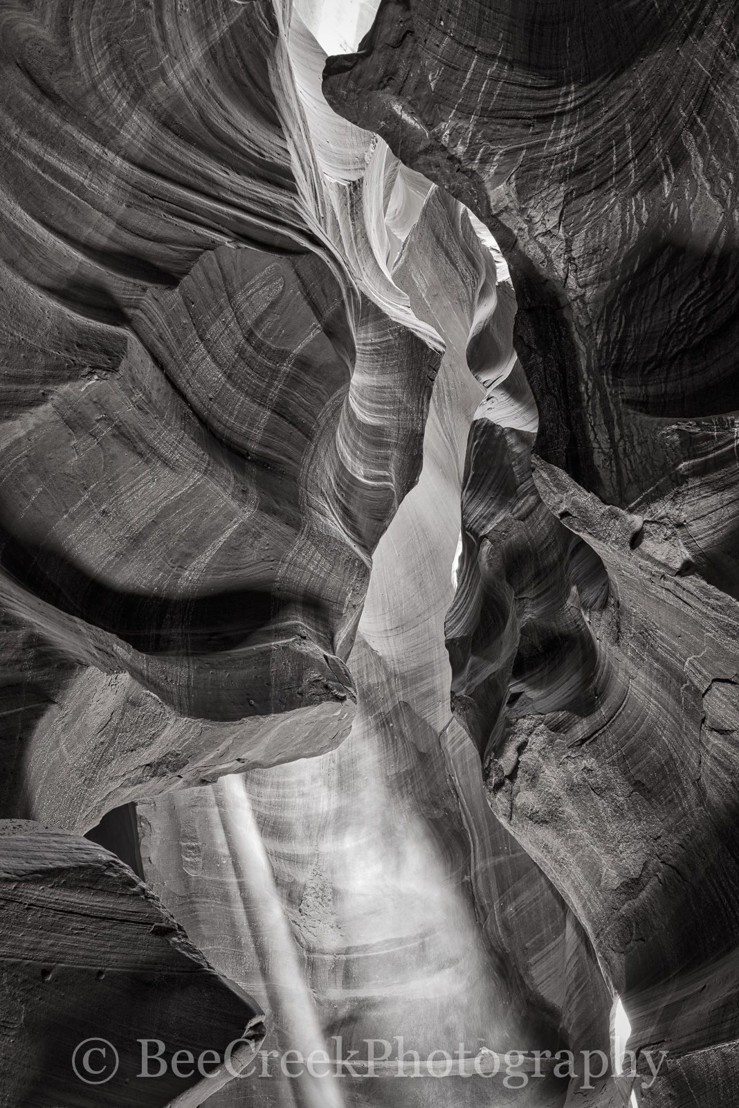 Slot Canyon BW-Only a gleam of light now exposes the carved out area of the slot canyonin this black and white. The...