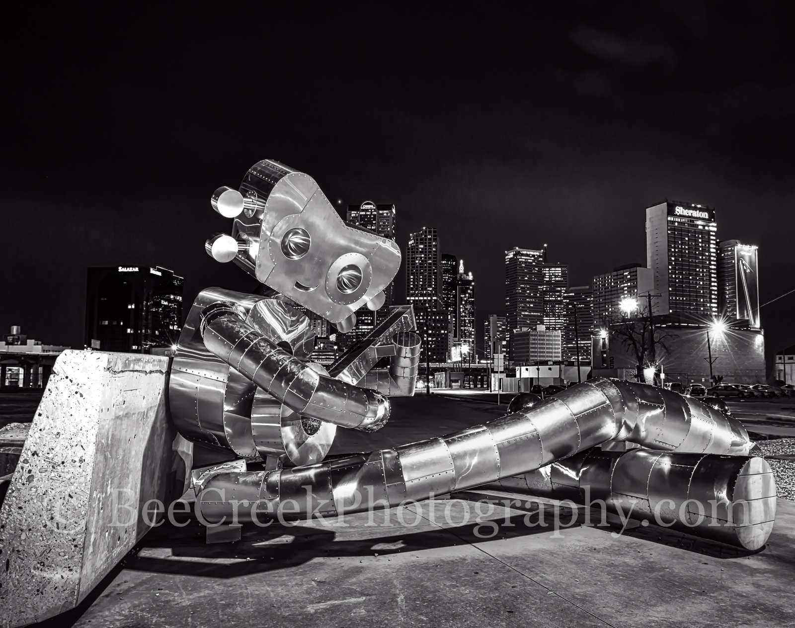 Dallas, traveling man, sitting sculpture, banjo, robo, skyline, skylines, cityscape, cityscapes, downtown,  modern, urban, night, robot, deep ellum, mass trasit, train, nuts, bolts, , photo