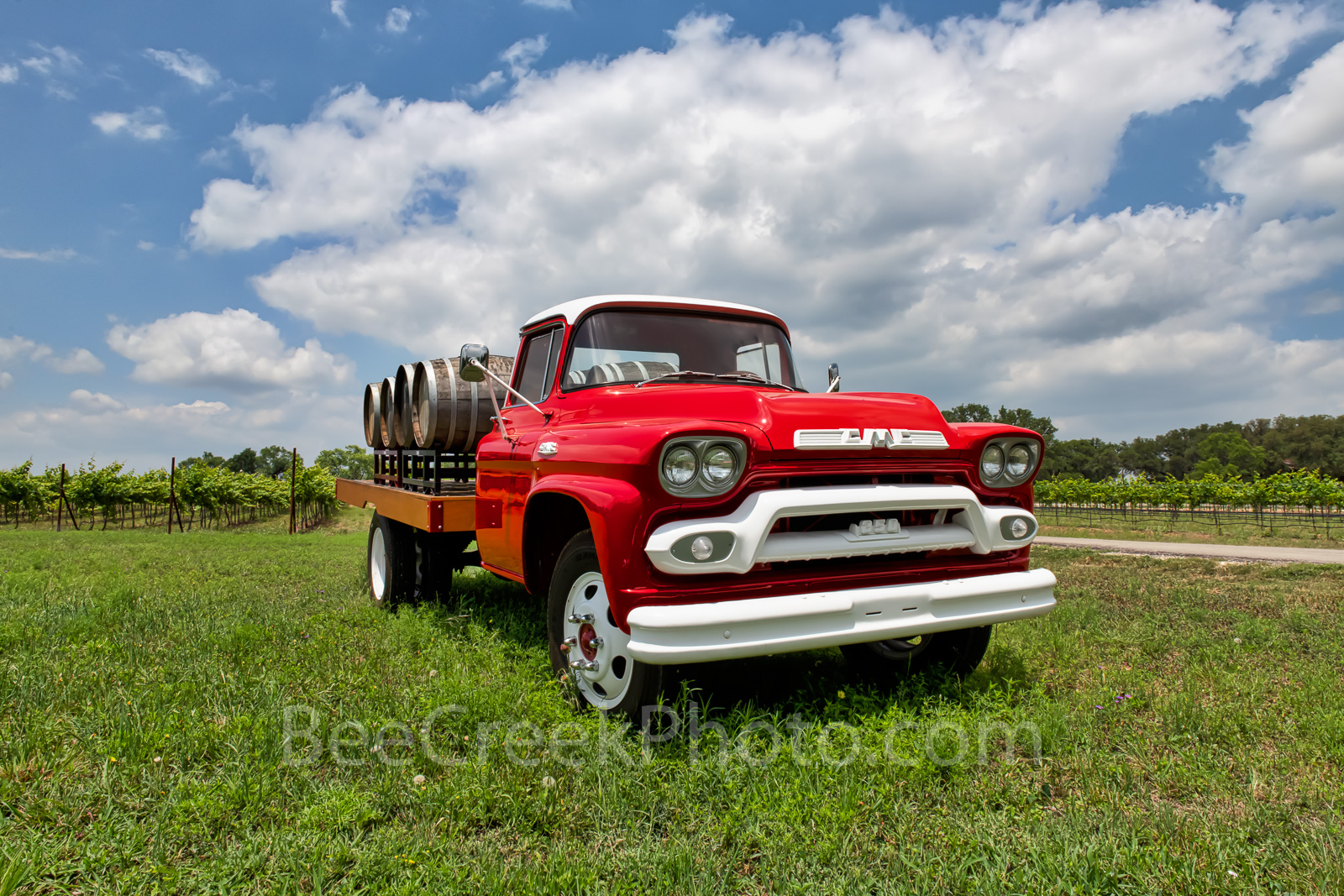 Hill country winery, bright red truck, wine, barrels, grapes, grape vines, clouds, blue sky, texas hill country, truck,, photo