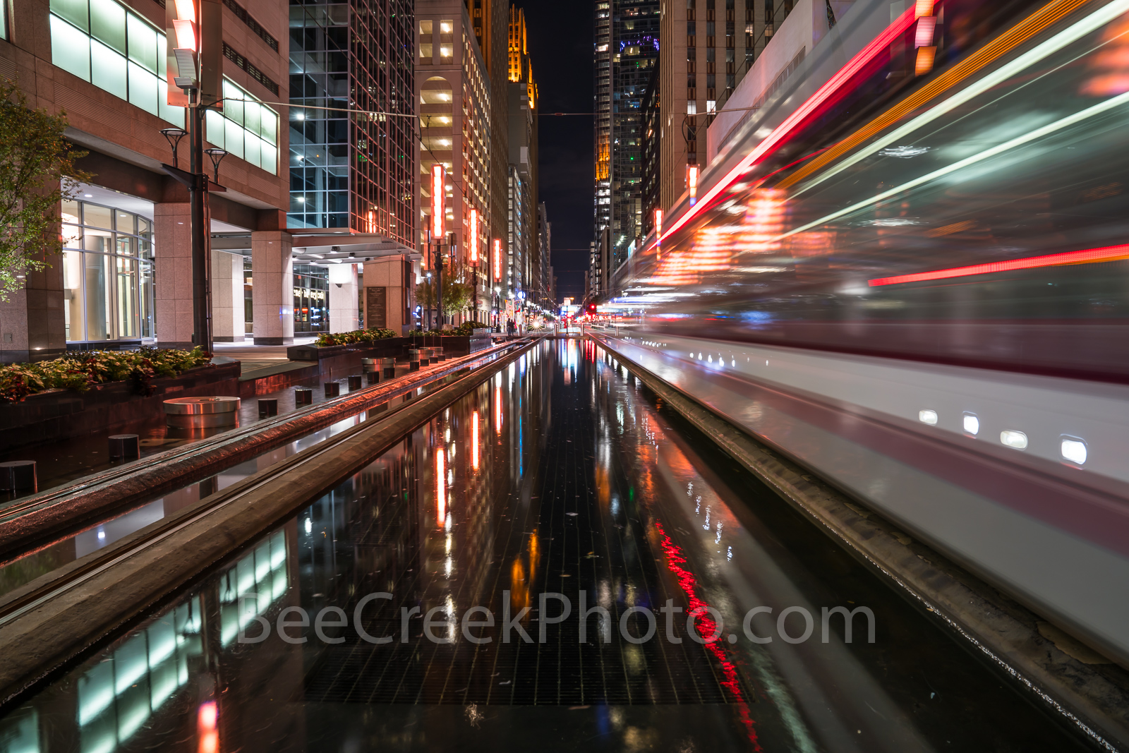 Houston Downtown Rail Night - This is image of the Houston rail system after dark as on of the trains zooms by in a...