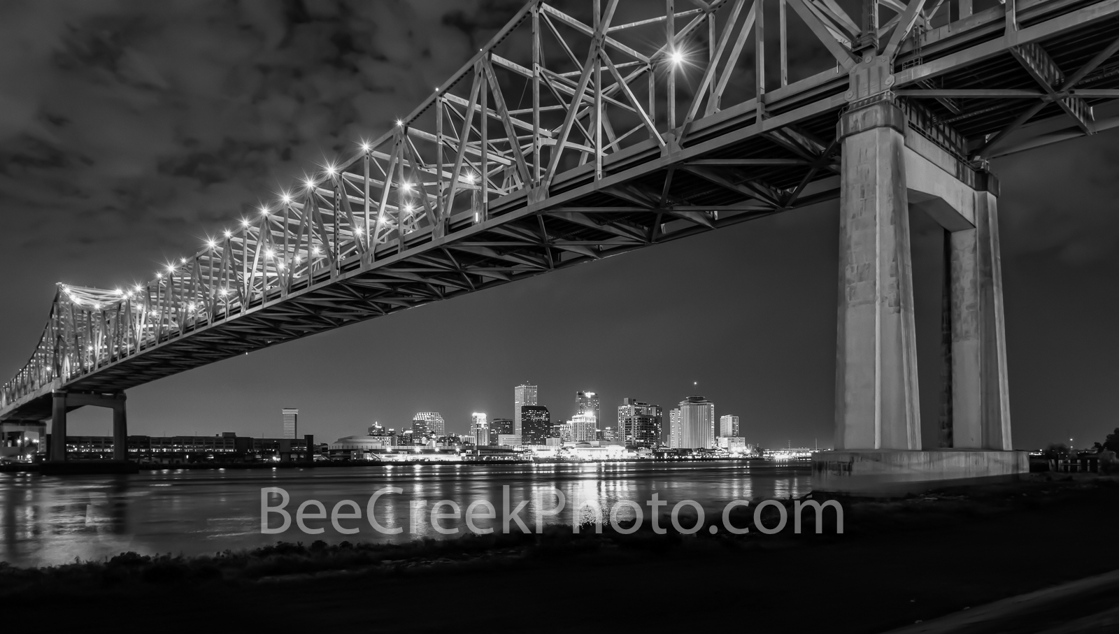 New Orleans Bridge Skyline BW-A view of New Orleans skyline from under the Mississippi bridge as the city was lite...