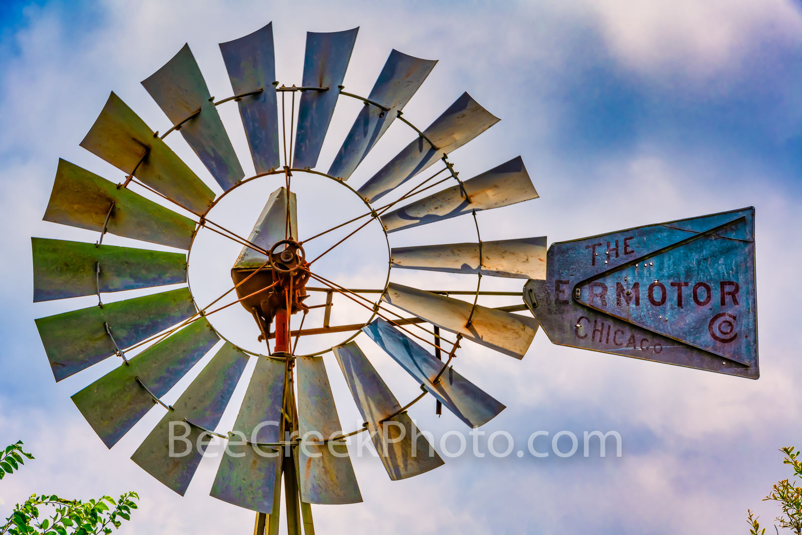 Rural Texas Hill Country Windmill - A texas windmill with cloudy skies in color showing the weathered blades and vanes of years...