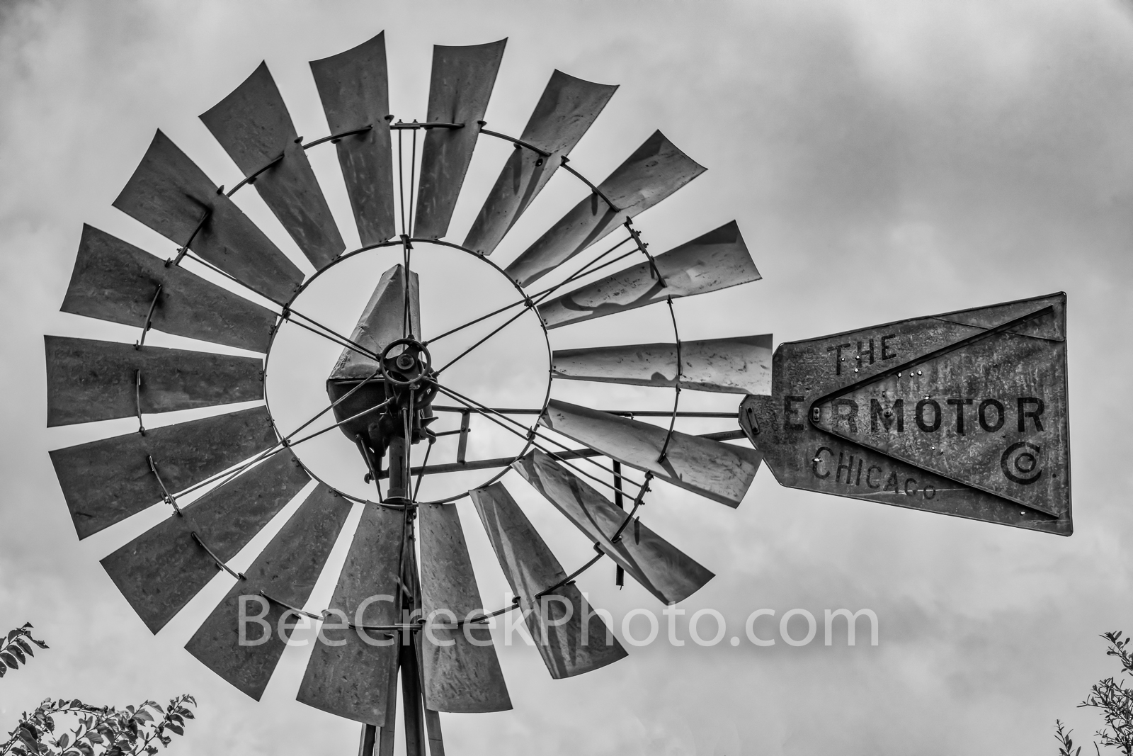 Rural Texas Hill Country Windmill BW - A texas windmill with cloudy skies in black and white showing the weathered blades and...