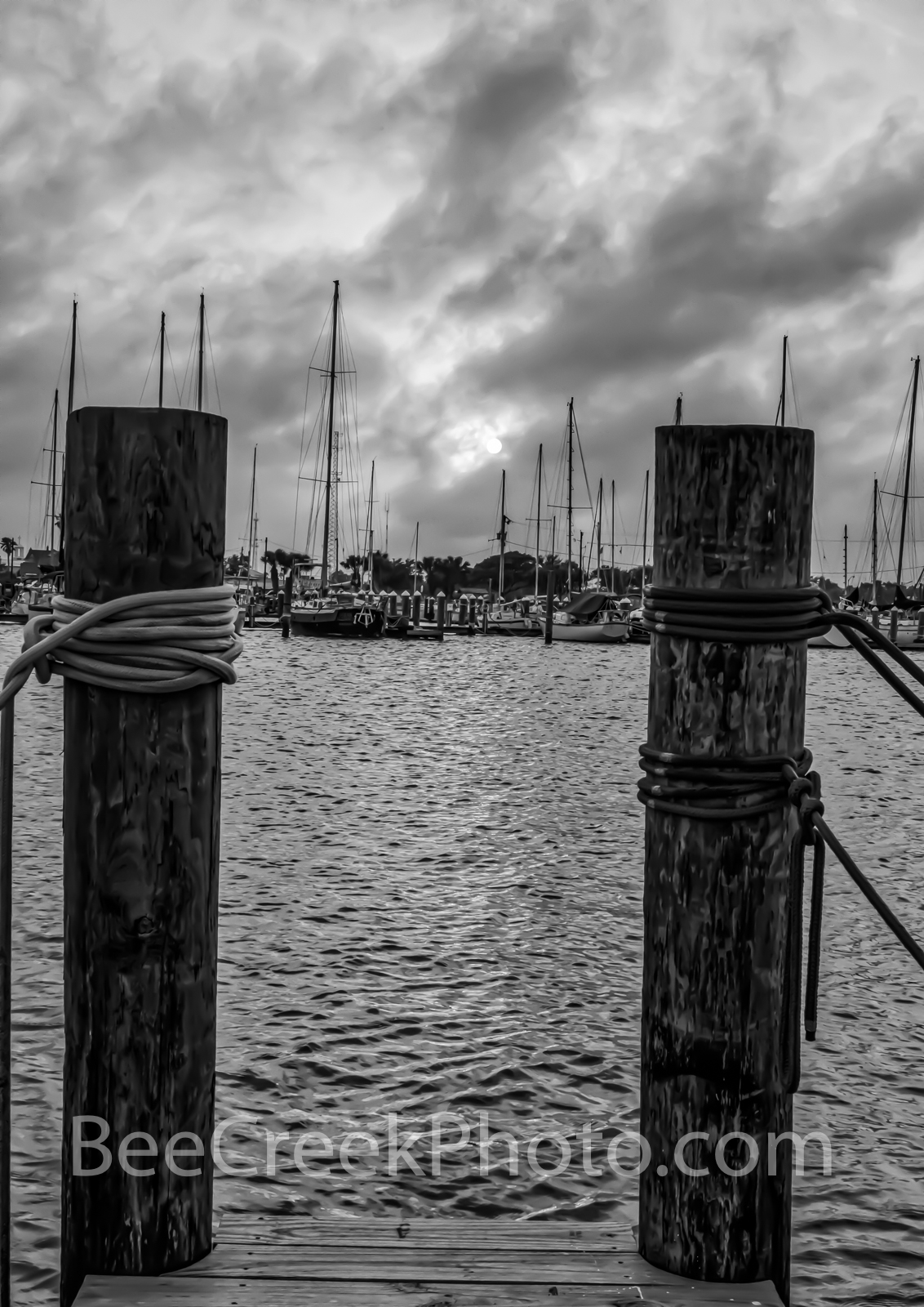 Sunset at Marina B W - A moody view through boat slip at sunset across the water of the marina in the bay at Rockport in...