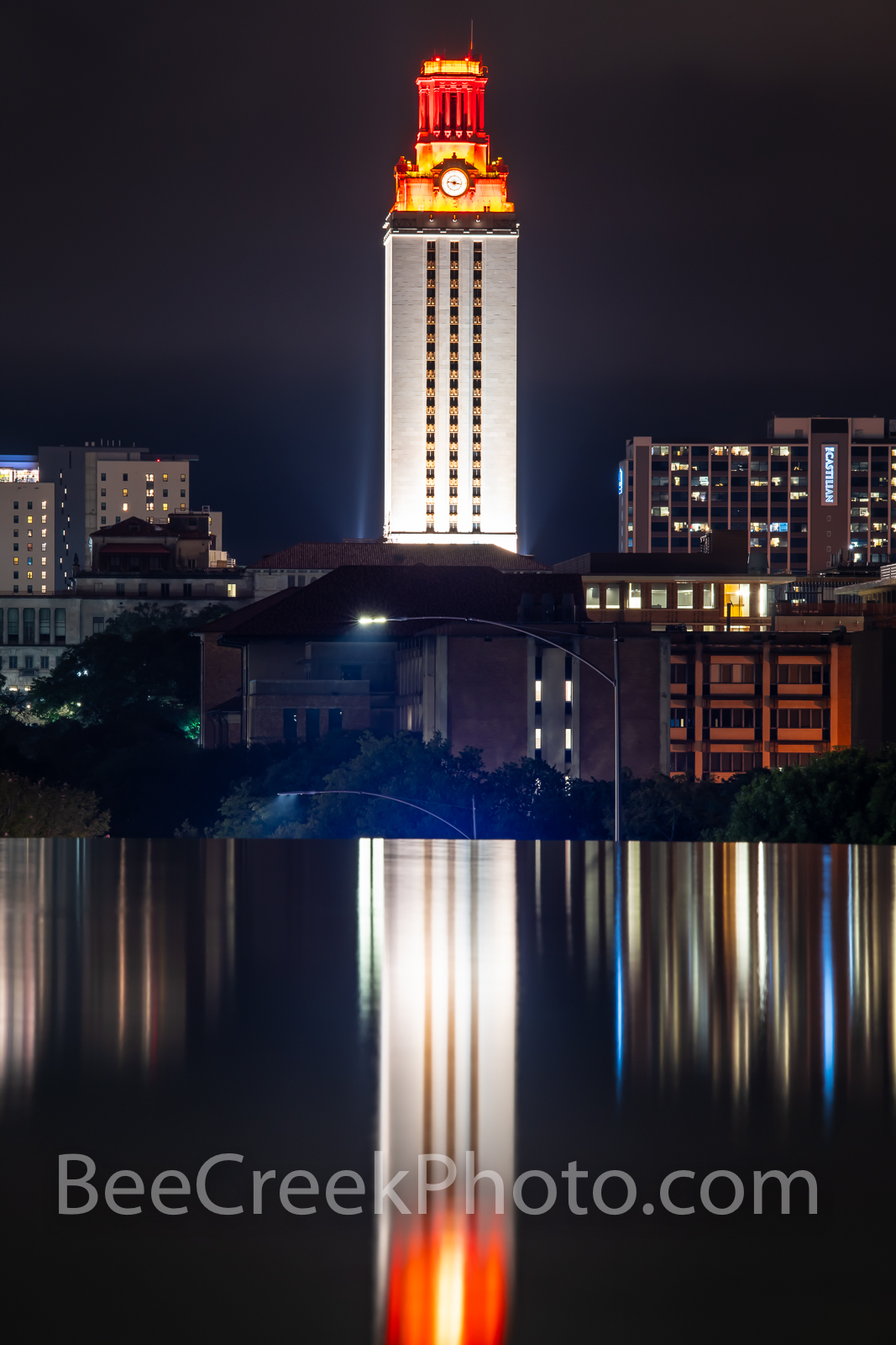 UT Tower Reflection Vertical  - This is U T Tower lit up at night as it reflects in the water feature near campus with the burnt...
